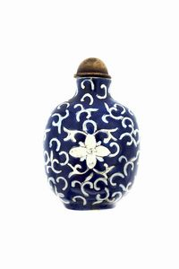 SNUFF BOTTLE - In ceramica bianca e blu decorata con volute. Reca scritta in ideogrammi cinesi sotto la base.  Cm 8x5